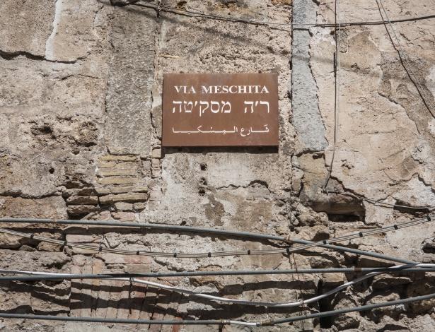 Placa de rua com escritos em árabe e hebreu, colocada na parede para sinalizar que a área uma vez foi ocupada por uma grande sinagoga