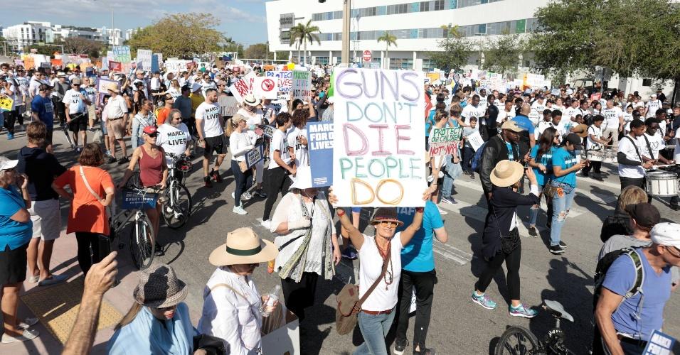 """24.mar.2018 - """"Armas não morrem, pessoas, sim"""", diz o cartaz levantado por esta mulher em Miami, no Estado da Flórida"""