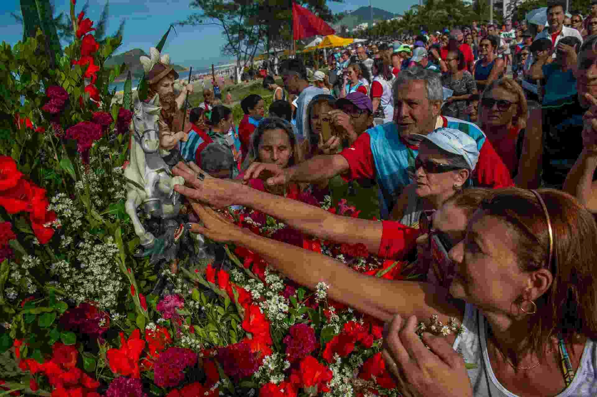 23.abr.2018 - Fiéis homenageiam o Dia de São Jorge durante celebração na Praia do Recreio dos Bandeirantes, zona oeste do Rio de Janeiro, nesta segunda- feira, 23. A data faz parte do calendário oficial do Rio de Janeiro e é feriado regulamentado desde 2008 - Ilan Pellenberg/Estadão Conteúdo