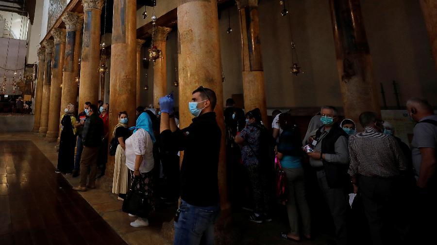 Turistas usam máscaras durante visita à Basília da Natividade, em Belém, por suspeita de coronavírus na região - Mussa Qawasma/Reuters