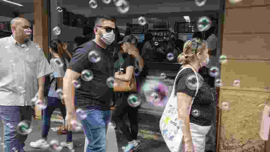 17.mar.2020 - Pedestres usam máscaras de proteção nas ruas de comércio de São Paulo - Andre Porto/UOL