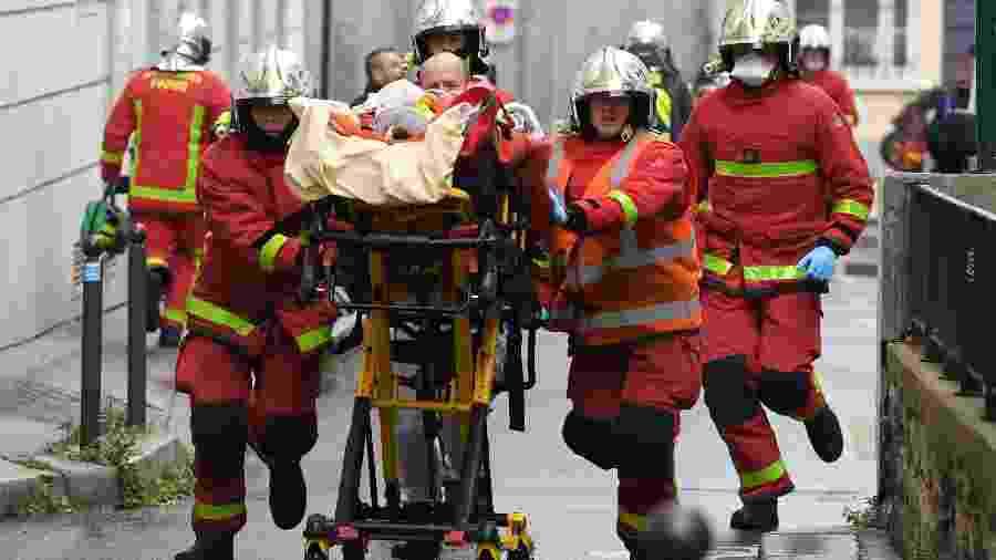 25.set.2020 - Bombeiros socorrem ferido após Ataque a faca perto da antiga sede do jornal Charlie Hebdo, em Paris - Alain Jocard/AFP