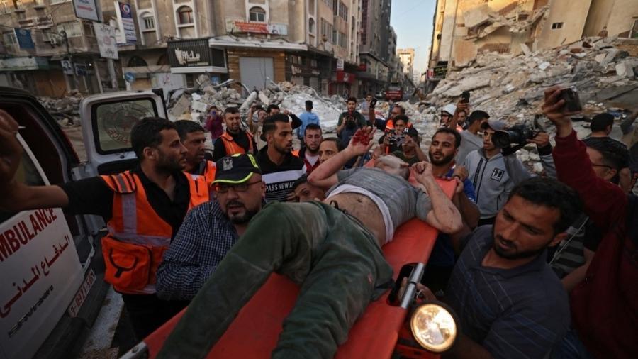 16.mai.2021 - Palestinos carregam sobrevivente de ataque a edifício em Gaza - Mohammed Abed/AFP