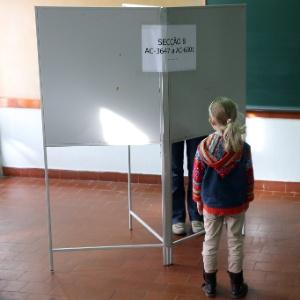 Criança espera a mãe votar em seção eleitoral em Lisboa