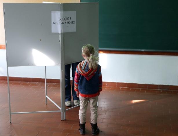 Criança espera a mãe votar em seção eleitoral em Lisboa, Portugal