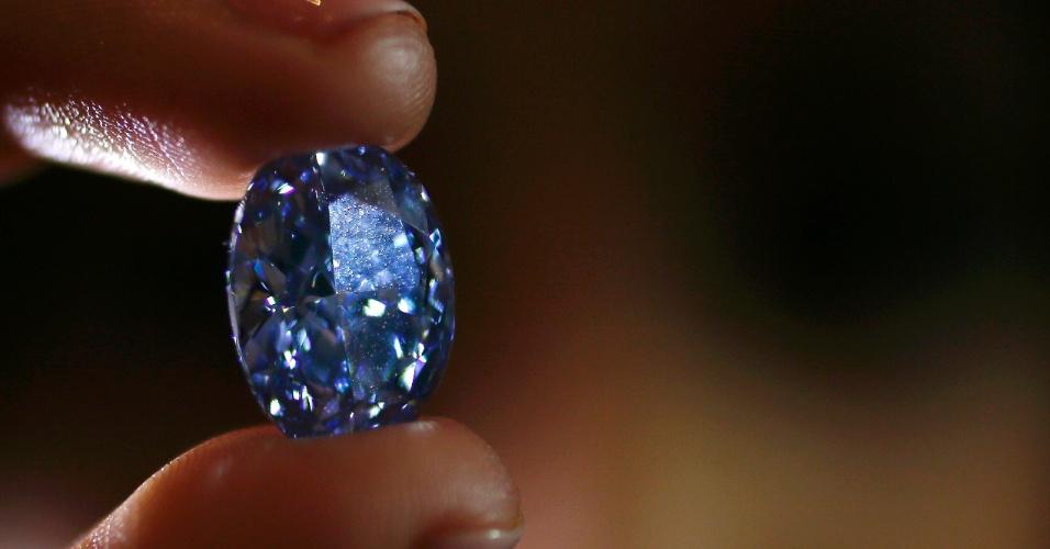 15.mar.2016 - Funcionária segura um diamante de 10,10 quilates na casa de leilões Sotheby no centro de Londres, na Inglaterra. O diamante azul deverá ser vendido por um valor entre US$ 30 milhões e US$ 35 milhões em um leilão em Hong Kong (China)
