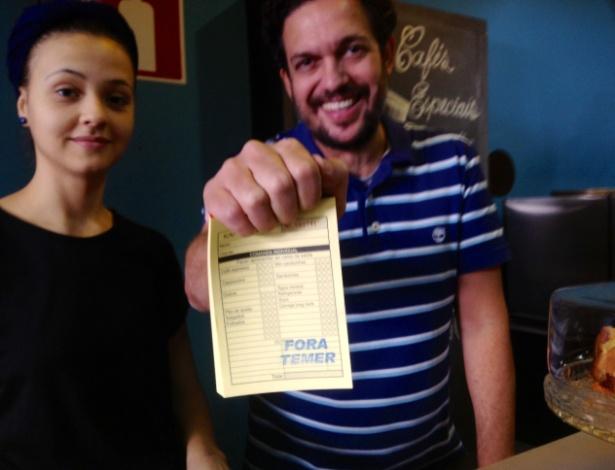 Ruimar Oliveira, 48, proprietário do Café Kahlúa, no centro de Belo Horizonte, com comandas do estabelecimento com a frase ?Fora, Temer?