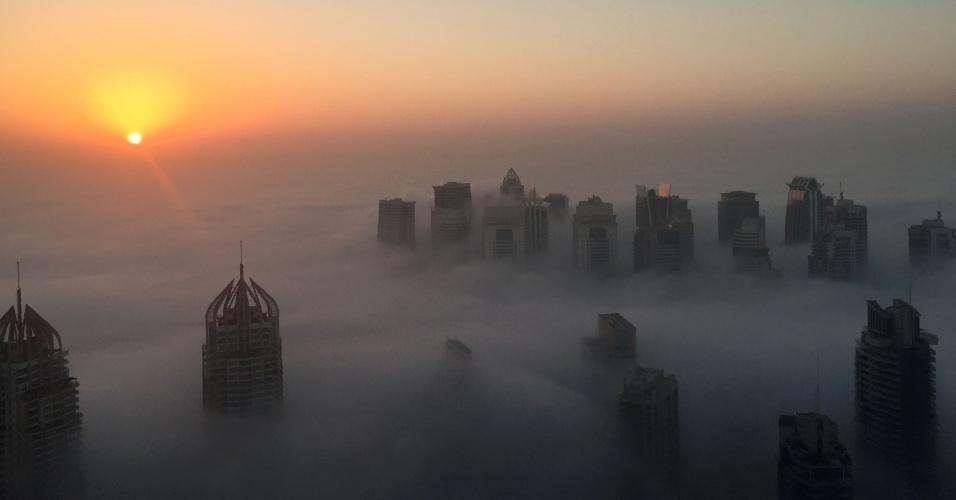 5.dez.2016 - Sol nasce atrás dos arranha-céus entre as nuvens em uma manhã com névoa em Dubai (Emirados Árabes Unidos)