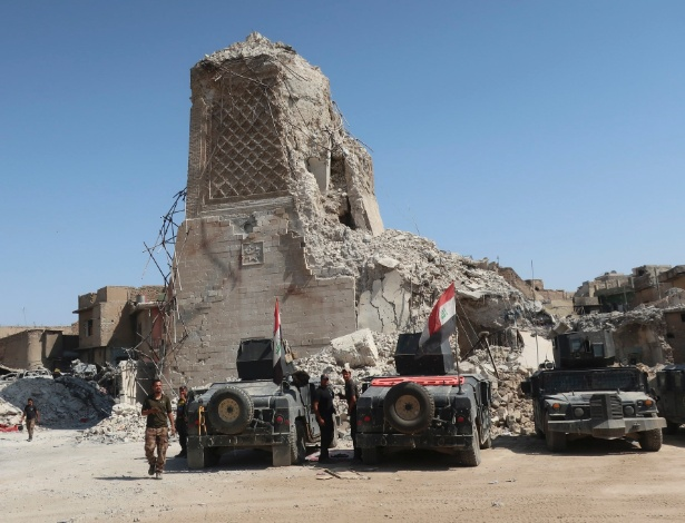 Soldados iraquianos caminham próximo ao que restou do minarete da Grande Mesquita Al Nuri, destruído pelo Estado Islâmico, em Mossul