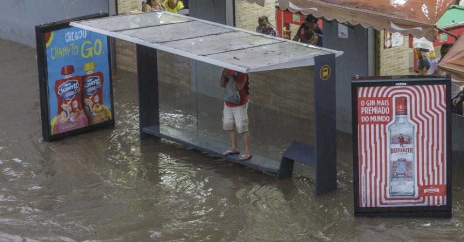 20.mar.2018 - Homem recorre à ponto de ônibus para fugir de alagamento na região do terminal Bandeira, no centro de São Paulo, após forte temporal