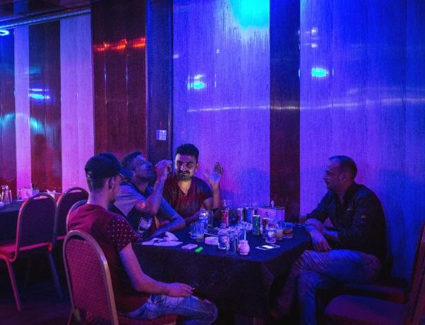 Homens bebem em bar na cidade de Mossul, no Iraque