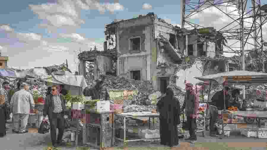 Camelôs vendem frutas e vegetais perto de ruínas em praça na cidade de Raqqa, na Síria - Ivor Prickett/The New York Times