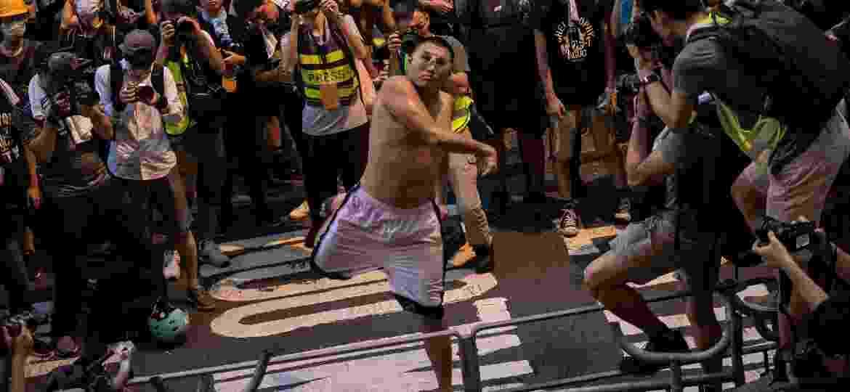 21.junho.2019 - Manifestante atira um ovo contra o quartel da polícia em Hong Kong. Segundo os organizadores, cerca de 2 milhões de pessoas se juntaram aos protestos e possuem uma sére de demandas, como a retirada de uma polêmica lei de extradição para a China e a libertação de presos políticos - AFP