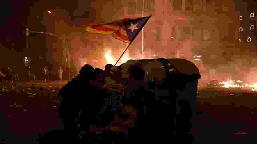 18.oct.2019 - Manifestantes se protegem de confrontos em Barcelona - Josep Lago / AFP