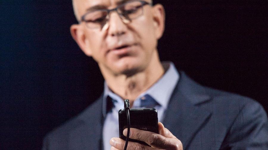 Jeff Bezos, chefe da Amazon, olha o primeiro celular de sua empresa - David Ryder/APF
