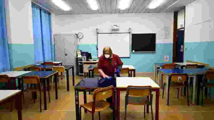 Uma faxineira limpa a sala de aula em escola para tentar conter um surto de coronavírus - Massimo Pinca/Reuters