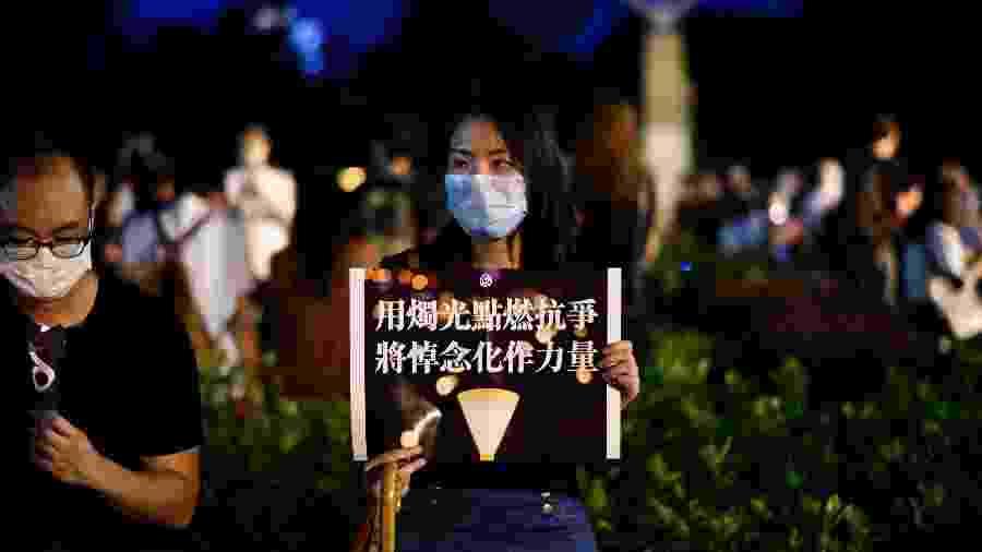 Ativista segura um cartaz durante uma lembrança à luz de velas do lado de fora do Victoria Park, em Hong Kong - Anthony WALLACE / AFP