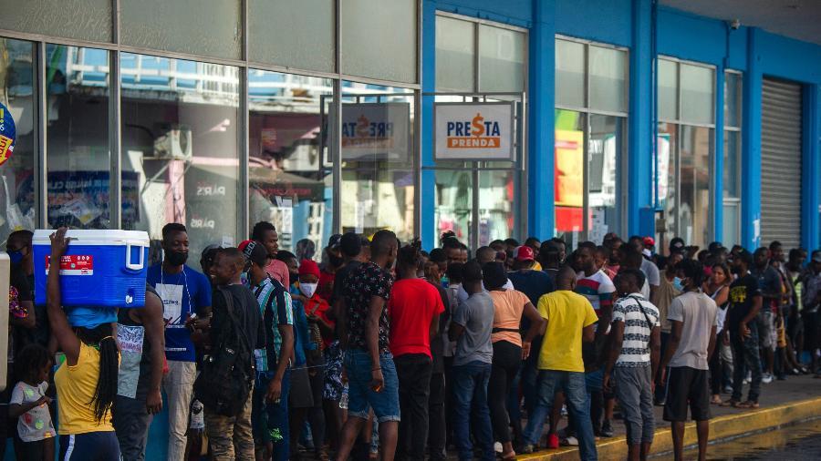 14.set.2021 - Imigrantes haitianos e centro-americanos aguardam a abertura de bancos para sacar dinheiro enviado por seus parentes em Tapachula, estado de Chiapas, México - Claudio Cruz/AFP