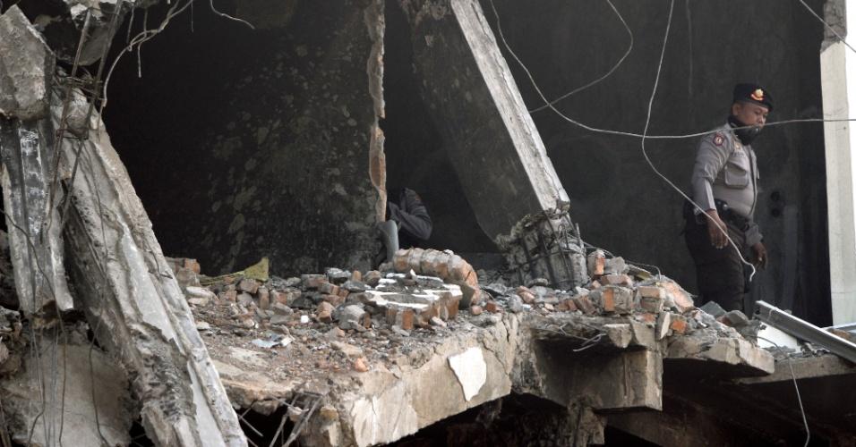 2.jul.2015 - Policial indonésio inspeciona um edifício em Medan, nesta quinta-feira (2), danificado pela queda de um avião C-130 Hercules da Força Aérea indonésia. A aeronave caiu em um bairro residencial e matou ao menos 142 pessoas, depois de uma falha em uma das turboélices