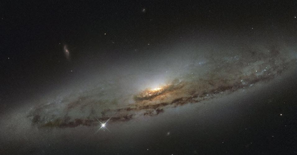 8.jan.2016 - A galáxia espiral NGC 4845, localizada a mais de 65 milhões de anos-luz de distância, na constelação de Virgem, foi registrada pelo telescópio espacial Hubble, da Nasa (Agência Espacial Norte-Americana). A orientação da galáxia revelou claramente sua estrutura impressionante, formada por um disco achatado, poeira machada e um bojo galáctico brilhante. O centro brilhante da galáxia hospeda um grande buraco negro, conhecido como supermassivo. Os cientistas estudam o comportamento das estrelas próximas ao buraco negro supermassivo para estimar a massa do buraco, que se estima ser centenas de milhares de vezes mais pesado que o Sol