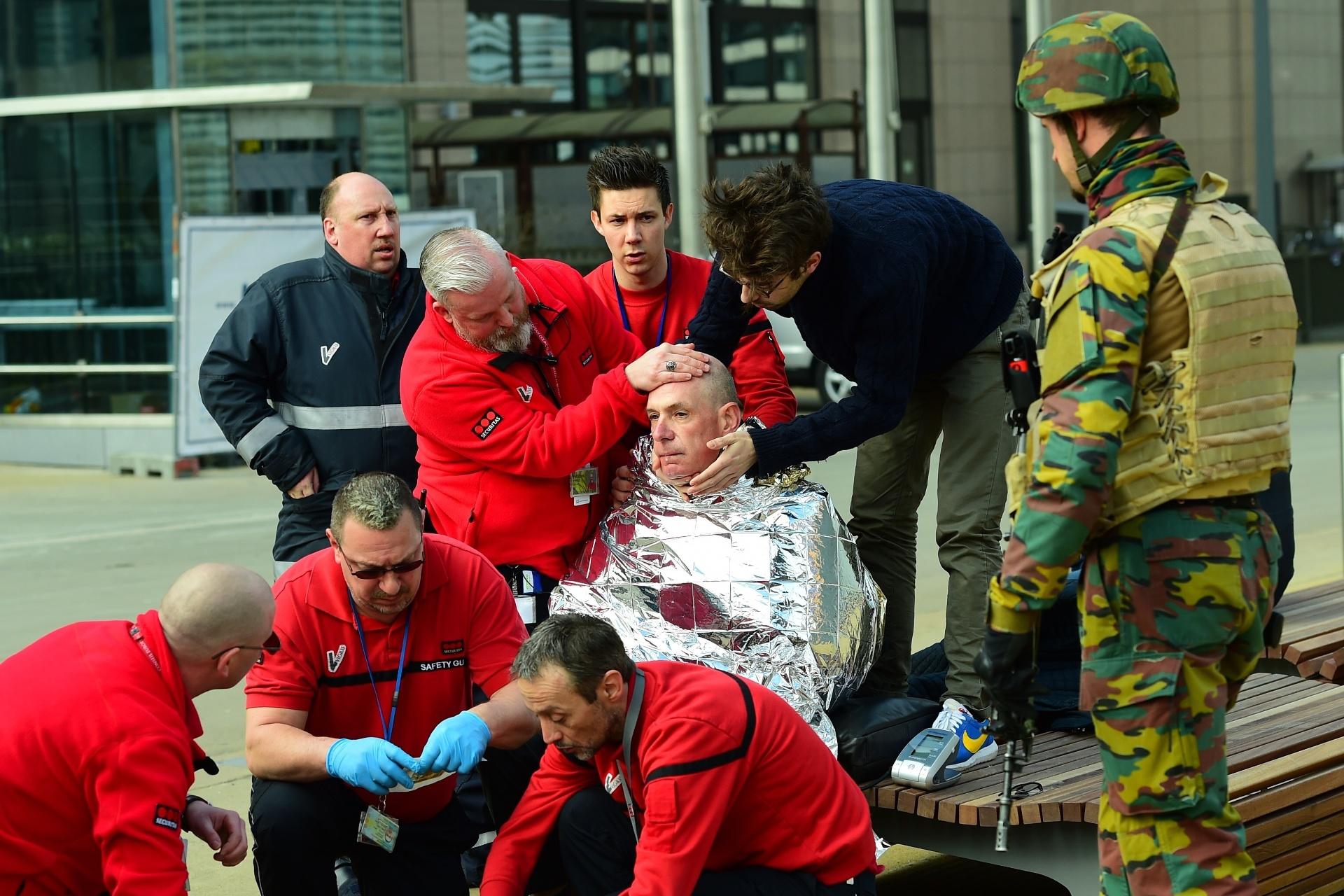 22.mar.2016 - Vítima é atendida nos arredores da estação Maalbeek, um dos alvos do atentado terrorista que atingiu a capital da Bélgica e sede da União Europeia, Bruxelas, na manhã desta terça-feira