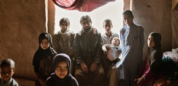 Nove dos dez filhos de Noor ul-Haq na casa da família no distrito de Behsud, no Afeganistão. O mais velho, Zia, no centro, viajou para Cabul para recolher o corpo do pai, que estava vivo