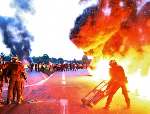25.mai.2016 - Policiais dispersam manifestantes que ergueram barricada em refinaria. O protesto é contra as reformas trabalhistas propostas pelo governo francês