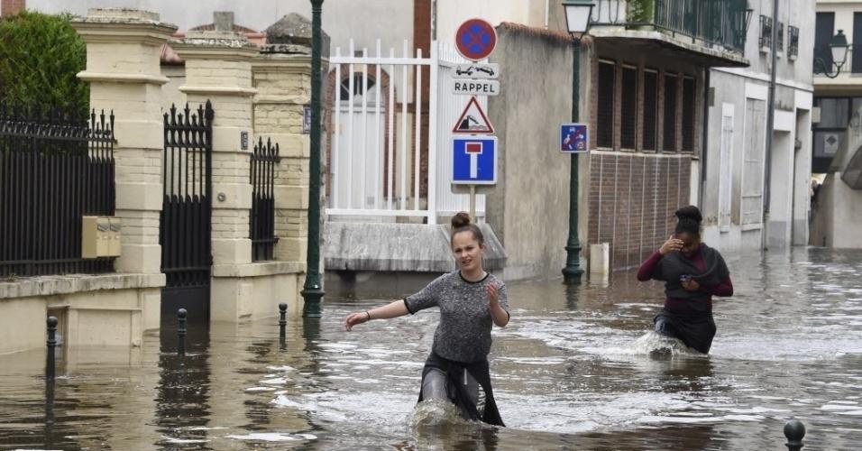 1º.jun.2016 - Mulher caminha por rua inundada em Montargis, sul de Paris, após fortes chuvas acabarem em alagamentos pela cidade. A França registrou sua primeira vítima, um homem de 74 anos que montava a cavalo morreu arrastado pelas águas no departamento de Seine-et-Marne, também ao sul da região de Paris, de acordo com as autoridades locais