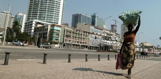 Mulher carrega alimentos em rua de Luanda, capital de Angola, um dos países mais pobres do mundo, com expectativa de vida estimada em cerca de 52 anos - AFP