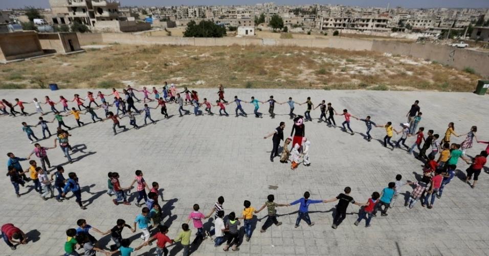 """27.jun.2016 - Alunos formam um círculo para comemorar o fim do ano escolar na """"Síria, Esperança"""", uma escola na periferia da área controlada por rebeldes na cidade de Maaret al-Numan, na província de Idlib. O prédio do colégio está danificado por ter sido usado por forças do governo como uma base antes dos combatentes rebeldes tomarem controle da área"""