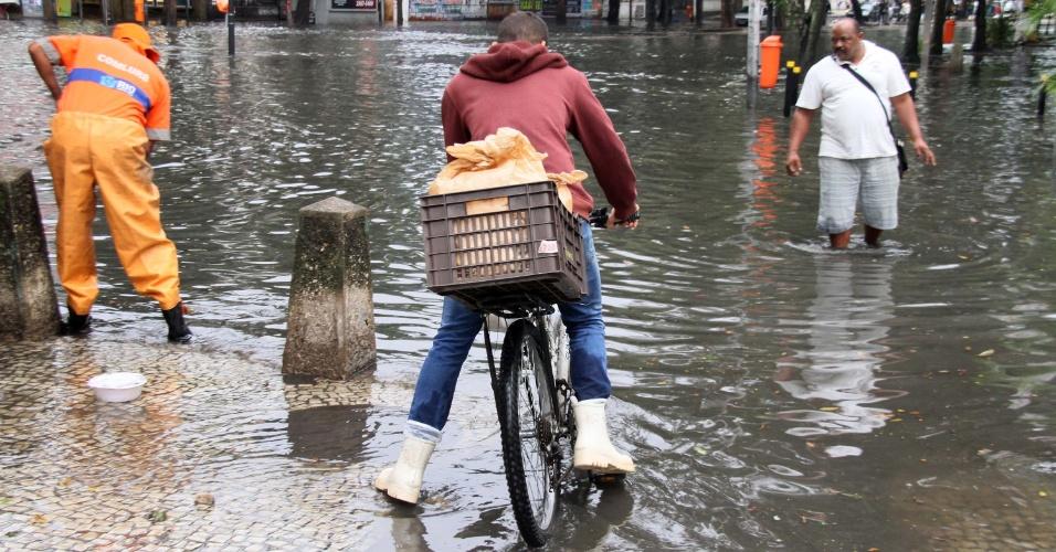 20.set.2016 - Choveu forte no Rio de Janeiro durante a madrugada desta terça-feira (20), o que provocou problemas em vários bairros, como alagamentos, bolsões d'água e queda de luz. Na imagem, pedestres enfrentam bolsão d'água na rua do Catete, na região central da capital fluminense