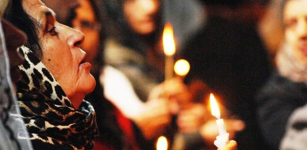 Mulher segura vela durante missa de Natal em Bartella, a 20 km de Mosul, no norte do Iraque, neste domingo