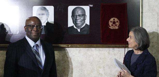 07.jun.2017 - Ao lado da presidente do STF, Cármen Lúcia (d), o ex-presidente da Corte, Joaquim Barbosa, é homenageado com uma foto sua na parede do Supremo