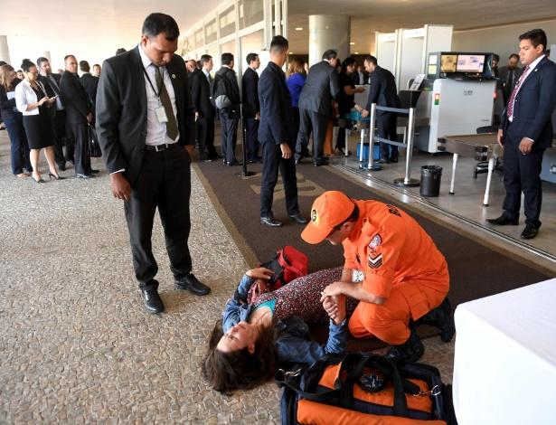 A mulher deitou no chão embaixo da rampa do prédio e recebeu auxílio