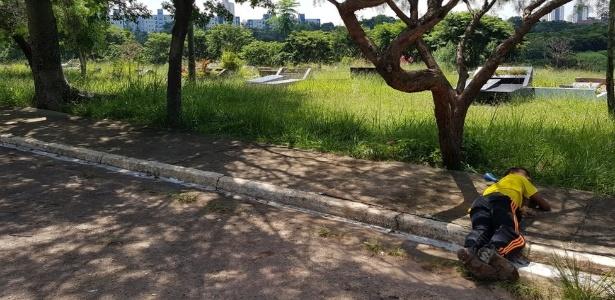 Homem dorme próximo a túmulos no cemitério da Vila Nova Cachoeirinha