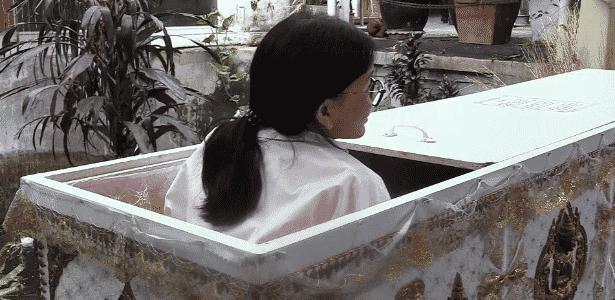 Cliente entra em caixão instalado no café Kid Mai, na Tailândia. Segundo o proprietário, ensinamento budista diz que quem pensa na morte se torna menos egoísta - EFE