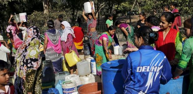 Moradores carregam recipientes com água após enchê-los em Nova Déli
