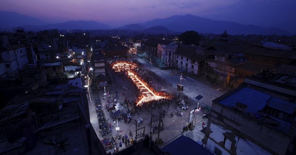 24.abr.2016 - Com velas acesas, nepaleses formam o desenho da torre de Dharara e do templo de Kasthamandap para marcar o um ano dos terremotos que devastaram o país, na praça de Bashantapur Durbar, em Katmandu, no Nepal