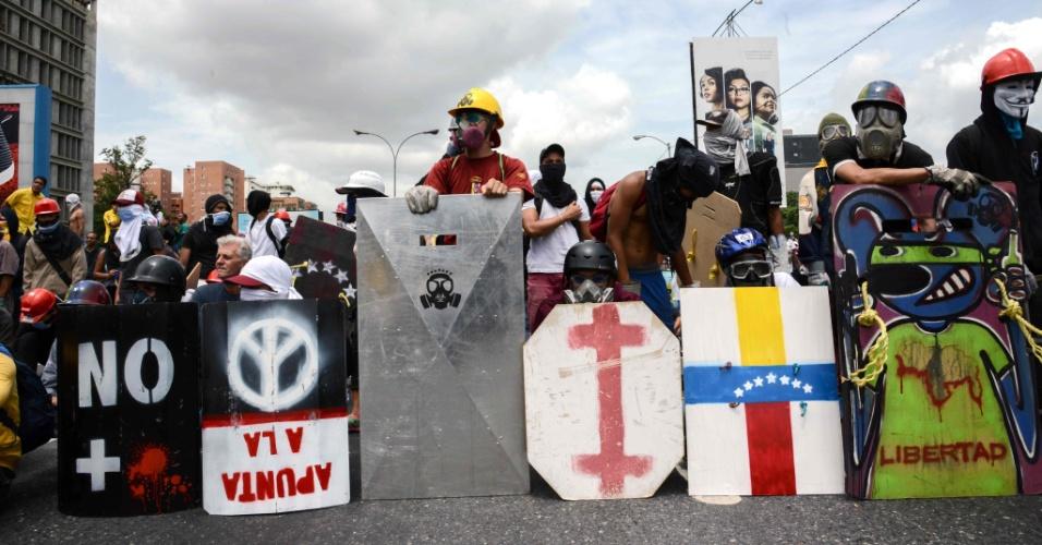 """31.mai.2017 - Para a linha de frente dos protestos, jovens mascarados carregam escudos de madeira e de metal para se protegerem das bombas de gás lacrimogêneo e das balas de borracha. Eles normalmente escrevem slogans nos escudos, como """"Resista, Venezuela""""."""
