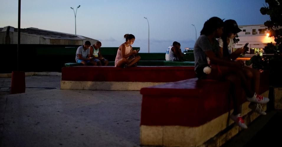 Jovens conectam-se à internet em uma praça de Havana