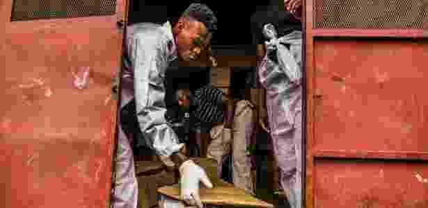Funcionários da Fundação St. Luke recolhem corpos abandonados da Funerária Zenith, em Porto Príncipe, no Haiti - DANIEL BEREHULAK/NYT - DANIEL BEREHULAK/NYT