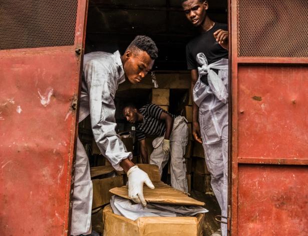 Funcionários da Fundação St. Luke recolhem corpos abandonados da Funerária Zenith, em Porto Príncipe, no Haiti