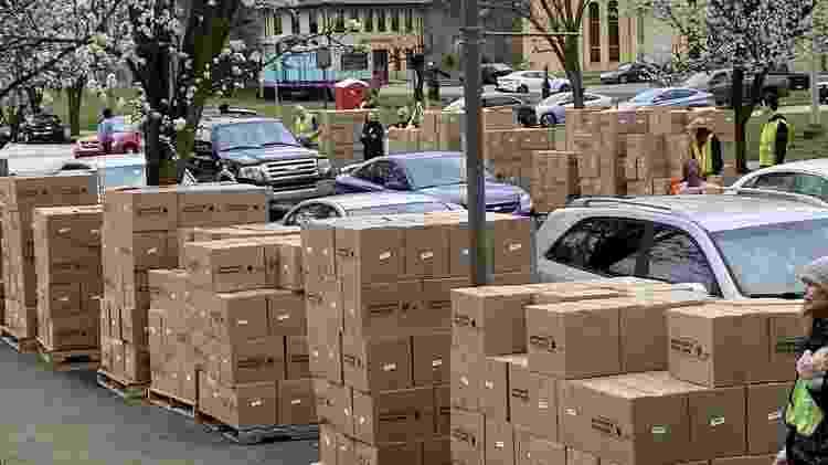 Muitos bancos de alimentos estão recorrendo à distribuição de comida em sistema de 'drive-thru', nos quais voluntários colocam uma caixa com mantimentos diretamente no porta-malas do carro - Greater Pittsburgh Community Food Bank - Greater Pittsburgh Community Food Bank