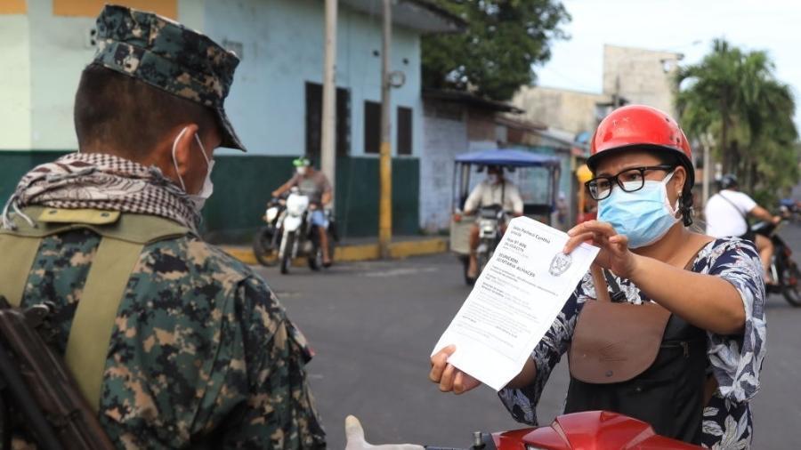 6.mai.2020 - Iquitos: por conta do lockdown no Peru, motociclista deve mostrar a militar sua autorização para estar na rua - Getty Images