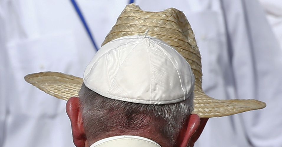 21.set.2015 - Papa Francisco é cumprimentado pelo presidente cubano Raúl Castro (de chapéu) ao chegar para celebrar uma missa em Holguín