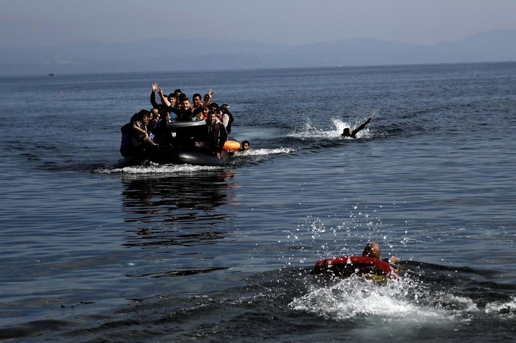 27.set.2015 - Refugiados acenam ao se aproximar da ilha grega de Lesbos neste domingo (27). Eles saíram de barco da Turquia e cruzaram o mar Egeu. Na mesma travessia, 17 sírios, incluindo cinco mulheres e cinco crianças, morreram afogados quando o barco em que viajavam naufragou, segundo a agência de notícias turca Dogan