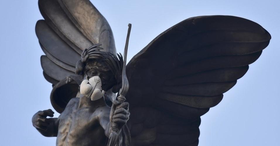 18.abr.2016 - Ativistas do Greenpeace colocaram uma máscara de gás no rosto da estátua de Eros em Piccadilly Circus, em Londres. Segundo a ONG, a intervenção é um protesto contra o aumento a níveis alarmantes da poluição atmosférica na capital britânica
