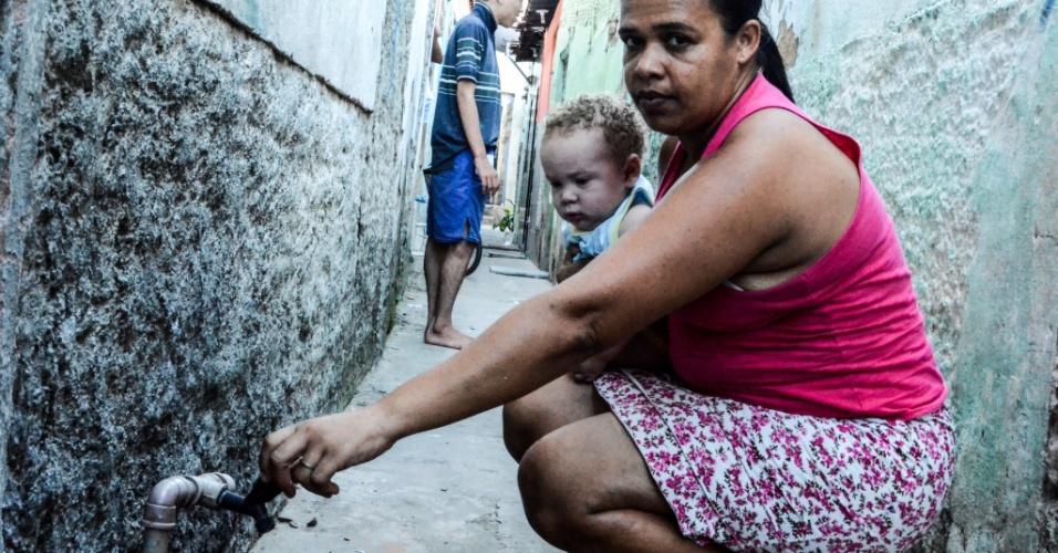 3.fev.2017 - Raquel Abelardo, 36, moradora do bairro da Levada, em Maceió, segura o neto em seu colo. A casa onde ela mora não possuí saneamento básico e o menino apresentava diversas picadas de insetos