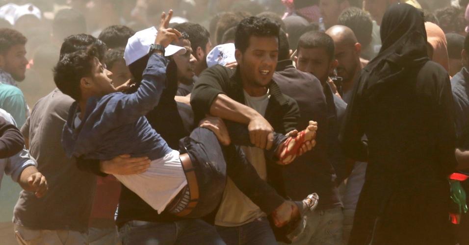 14.mai.2018 - Palestinos carregam homem ferido durante confrontos com forças de Israel na Faixa de Gaza. Palestinos protestam contra a inauguração da embaixada dos EUA em Jerusalém