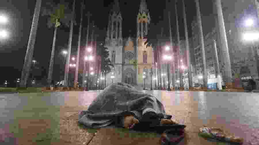 Morador de rua se abriga do frio enquanto dorme durante a madrugada frente da Cadetral da Sé, no centro de São Paulo - Alex Silva/Estadão Conteúdo
